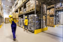Warehouse worker carrying a box and a manager controlling products on the floor